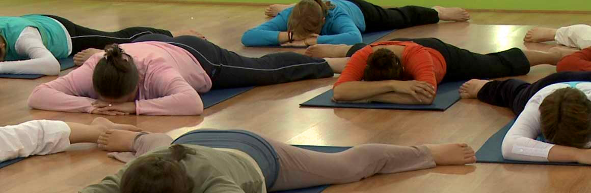 Multiple Dru yoga participants lying face down with head in hands and legs spread - the crocodile pose
