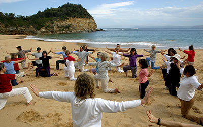 Dru yoga - group performing the Seat of Compassion sequence on the beach