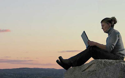 Woman studying on laptop in nature