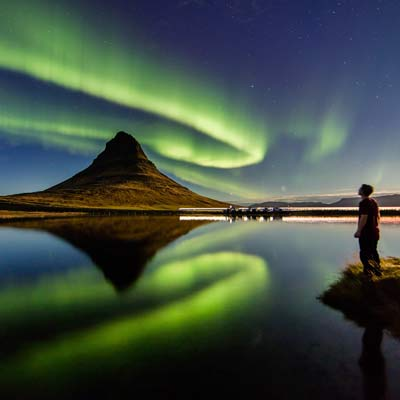 Man by water watching northern lights