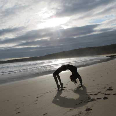 Dru yoga - chakrasana posture at the beach