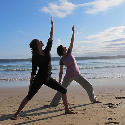 Dru yoga - warrior posture on the beach