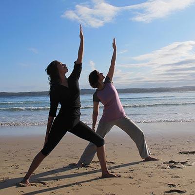 Dru yoga - warrior posture on the beach