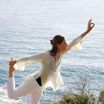 Dru yoga - dancer posture (natarajasana) by the beach