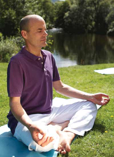 Man meditates by pond