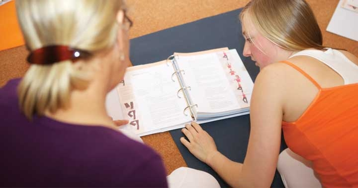 Yoga students studying teacher training course manuals