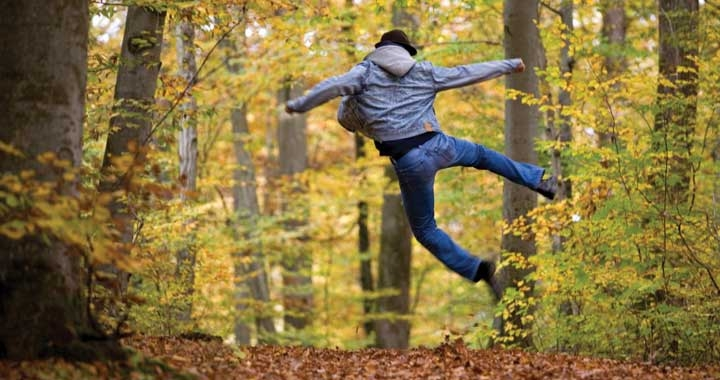 Man jumping for joy in forest path