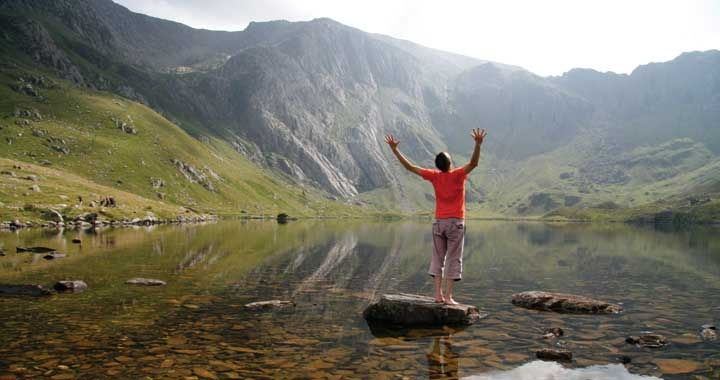 Dru Yoga teacher standing by lake