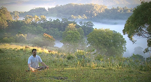 person meditating at the top of a hill in nature