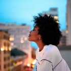 woman-meditating-colourful-city-background